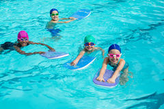 Little swimmers with kickboards enjoying in pool Stock Image