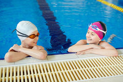 Little Swimmers in Pool. Cheerful boy and girl smiling and talking while taking a break after swimming holding onto pool border Stock Photo