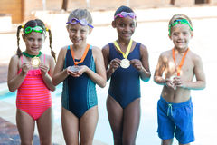 Little swimmers showing medals at poolside Royalty Free Stock Image
