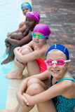 Little swimmers sitting at poolside. High angle view of little swimmers sitting at poolside Stock Photography