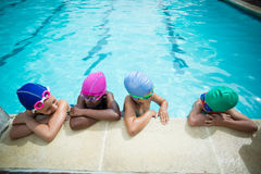 Little swimmers talking while leaning at poolside Stock Image