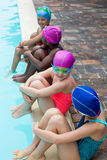 Little swimmers talking while sitting at poolside Royalty Free Stock Photos