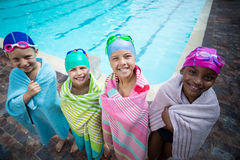 Little swimmers wrapped in towels standing at poolside Stock Photo