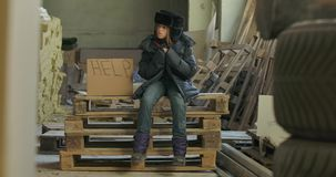 Little Syrian refugee in dirty warm clothes sitting on pallets at the construction site with Help cardboard. Lonely
