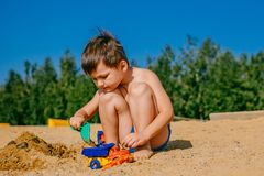 Little tanned boy playing on a sandy beach royalty free stock image