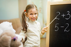 Little teacher. Beautiful young girl is teaching toys at home on blackboard. Stock Photo
