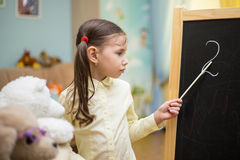 Little teacher. Beautiful young girl is teaching toys at home on Stock Photo
