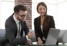 Two coworkers working on new business strategy. Little team of businesspeople smiling and looking together at computer Royalty Free Stock Images