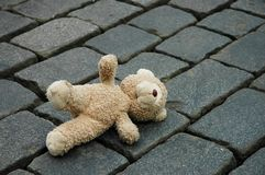Little teddy-bear. Laying on the cobblestone pavement Stock Image