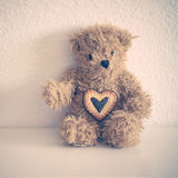 Little teddy bear sit down with heart cookie Stock Image