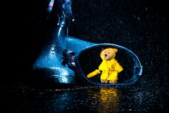 Little Teddy in a yellow rain coat. Little Teddy in a raincoat finds refuge in blue wellies Stock Photos