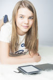 Little teenage girl with e-book at home Stock Photos