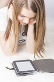 Little teenage girl with e-book at home Stock Image