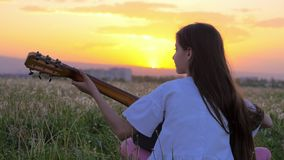 Little teenager girl playing the guitar. beautiful summer landscape at sunset. art Music Concepts. dandelions field near the town. Little teenager girl playing stock video