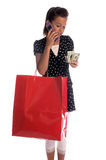 Little Tele Shopper. Twelve, 12 year old girl with a big red shopping bag and a handful of cash talking on a cell phone Royalty Free Stock Images