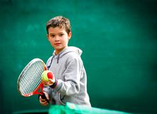 Little tennis player on a blurred green background. Little tennis player on a blurred green background Stock Photo