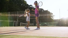 Little tennis player giving five to cute female coach and hugging after tennis training on the court. Little tennis player giving five to cute female coach and stock video