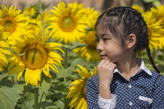Little Thai girl in sunflower field. Royalty Free Stock Photography