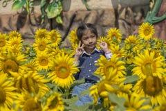 Little Thai girl in sunflower field. Royalty Free Stock Photo