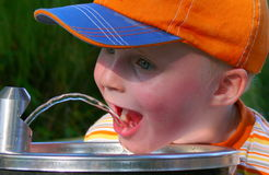 Little thirsty boy. This is my 3-year-old son on a hot day at the playground trying to drink from the water dispenser Stock Image
