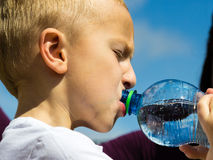 Little thirsty boy child drink water from bottle Stock Image