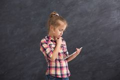 Little thoughtful girl with tablet on dark background. Little thoughtful girl playing online games on tablet. Female child posing on dark background. Social Royalty Free Stock Photo