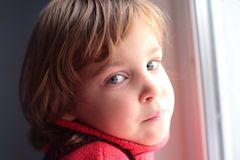 Little thoughtful girl at window Stock Photography