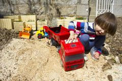Little boy playing with toy digger and dumper truck. Little three year old boy playing in the sand with a digger and dump truck Royalty Free Stock Photography