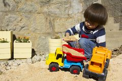Little boy playing with toy digger and dumper truck. Little three year old boy playing in the sand with a digger and dump truck Stock Images