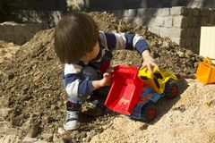 Little boy playing with toy digger and dumper truck. Stock Photos