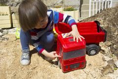 Little boy playing with toy digger and dumper truck. Little three year old boy playing in the sand with a digger and dump truck Stock Photos