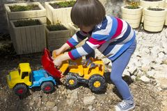 Little boy playing with toy digger and dumper truck. stock photography