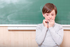 Little thrilled pupil standing at blackboard Stock Images