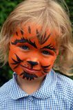 Little tiger girl. Little preschooler wearing a school uniform on a school fair, with her face painted in black and orange, pretending she's a tiger Stock Image