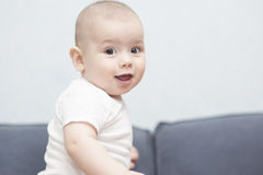 Little tiny baby standing on sofa Stock Images
