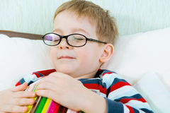 Little tired boy sleeping with book in bed Royalty Free Stock Photo