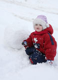 Little tired girl sits on snow near big snowball Royalty Free Stock Photography