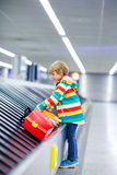 Little tired kid boy at the airport, traveling. Cute little tired kid boy at the airport, traveling. Upset child waiting with kids suitcase on baggage carousel Royalty Free Stock Photos