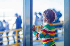 Little tired kid boy at the airport, traveling. Cute little tired kid boy at the airport, traveling. Upset child waiting near window and looking at plane Royalty Free Stock Photography