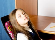 Little tired pretty girl. With long hair sitting in a chair Stock Photo