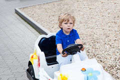 Little todder boy playing with big toy car Royalty Free Stock Image