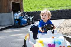 Little todder boy playing with big toy car Stock Photos