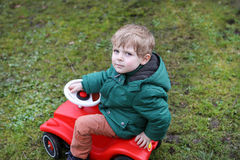 Little todder boy playing with big toy car Stock Image