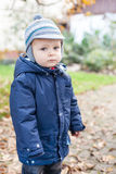 Little toddler in autumn garden in warm clothes. Cute lovely toddler boy in autumn garden in warm clothes stock image