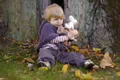 Little toddler in an autumn park with little dogs Royalty Free Stock Image