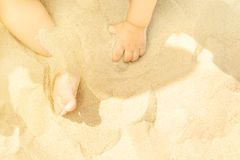 Little Toddler Baby Playing on Beach by the Sea. Small Hands Feet in Sand. Sunny Summer Day. Vacations Childhood Parenting Charity. Childcare Safety Purity royalty free stock photo
