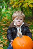 Little toddler with big orange pumpkin in garden Stock Image
