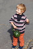 Little toddler with big orange pumpkin in garden Stock Photos