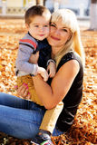 Little toddler boy in autumn park with his mother Stock Photo