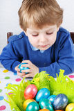 Little toddler boy being happy about selfmade Easter egg in kind Stock Photos